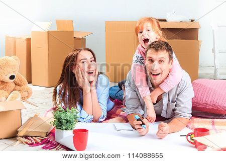 The happy family  at repair and relocation. The family planing  to accommodation on a background of boxes poster