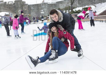 Ice skating couple having winter fun on ice skates Quebec, Canada.