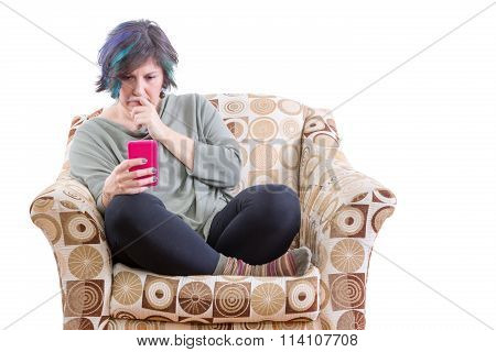 Concerned Woman In Sofa Looking At Phone