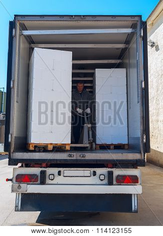 Worker Loads White Semi-truck