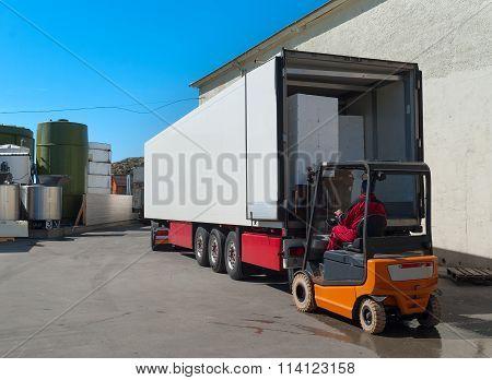 Worker On Loader Loads White Semi-truck