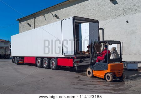 Worker On The Loader Unload White Semi-trailer