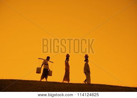 Silhouette of Asian traditional farmers carrying clay pots on head going back home, Bagan, Myanmar