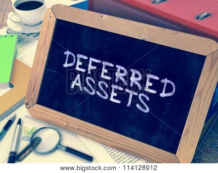 Deferred Assets - Chalkboard with Hand Drawn Text, Stack of Office Folders, Stationery, Reports on Blurred Background. Toned Image. poster