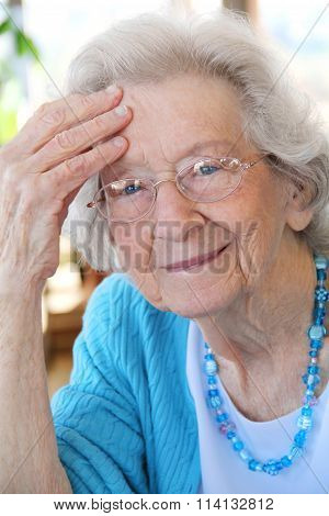 Elderly Woman with Glasses Thinking and Smiling