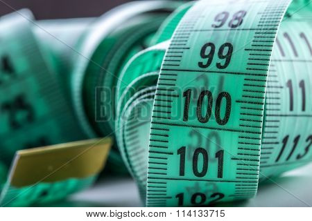 Curved measuring tape. Measuring tape of the tailor. Closeup view of green measuring tape. Tape measure as symbol of healthy lifestyles. poster