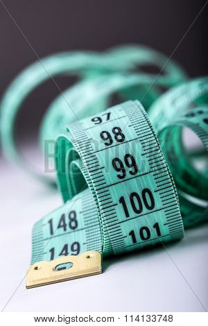 Curved measuring tape. Measuring tape of the tailor. Closeup view of green measuring tape. Tape meas