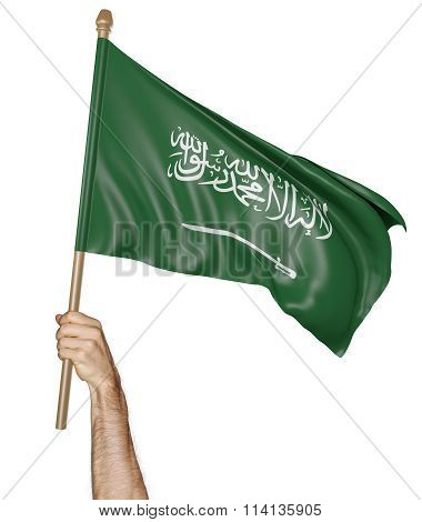 Hand proudly waving the national flag of Saudi Arabia