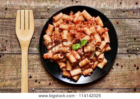 high angle shot of a black plate with penne rigate with bolognese sauce on a rustic wooden table