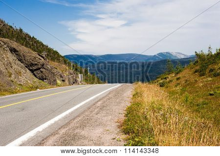 Empty Paved Road And Gravel Shoulder Against Hills And Mountains