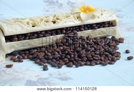 Roasted coffee beans spill out of the box.