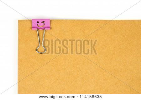 Happy face paperclip nipped at brown paper on white background.