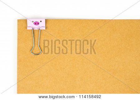 Happy pig face paperclip nipped at brown paper on white background.