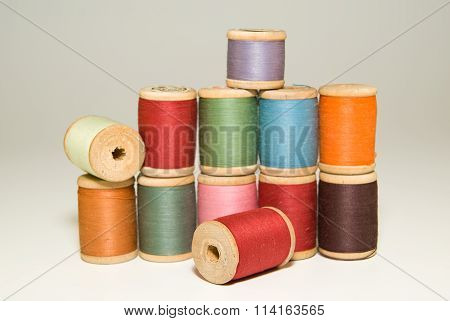 Many Spools Of Thread Of Different Colors On A White