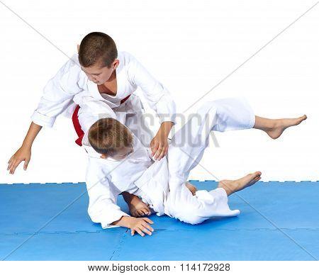 Children are training throws of judo in judogi