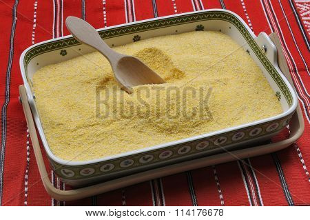 Uncoocked hominy grits in rectangular bowl on a red traditional romanian towel