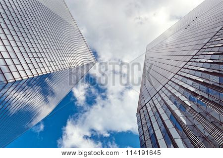 NEW YORK - AUGUST 27: Looking up the modern glass facade of the new One World Trade Center built at Ground Zero, New York to blue sky and clouds. August 27, 2015 in New York.