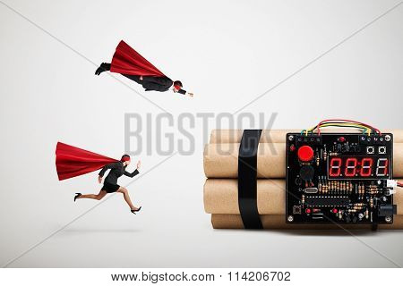 superman and superwoman hurry to defuse the bomb over light grey background