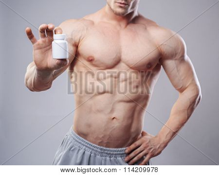Bodybuilder with a white jar of pills on neitral background. Studio shot