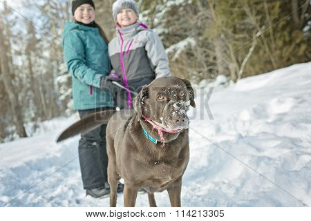 girls with dog in winter park
