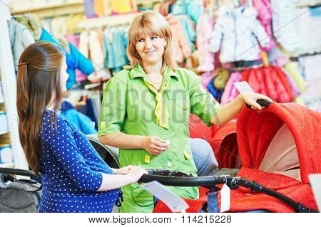 Pregnancy shopping. Female saleswoman selling perambulator for baby carriage to young pregnant woman at shop store