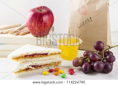 Lunchbox In School: Sandwich With Peanut Butter And Jam, Apple, Grapes, Jelly On A White Wooden Back