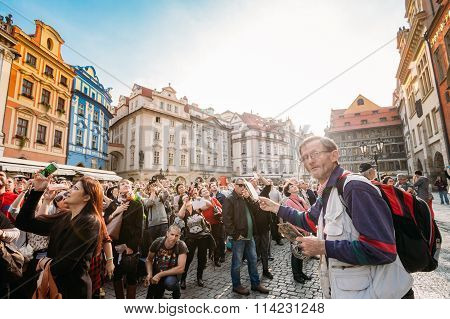 Group of tourists taking photo of town hall with astronomical cl