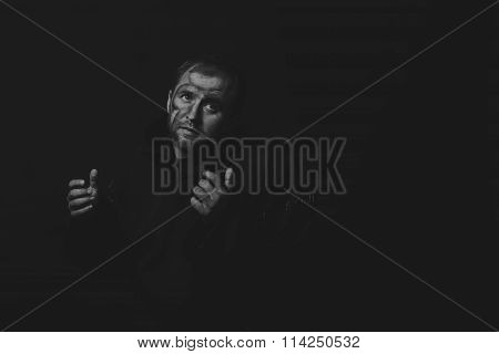 Beautiful and fascinating game theater actor on camera. Black and white photo of the actor in the guise of a beggar on a dark background. Beautifully decorated stage image and professional makeup.