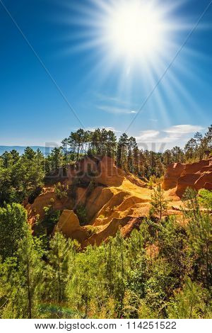 Green trees create contrast with the ocher. Roussillon, Provence Red Village. Multi-colored ocher outcrops - from yellow to orange-red