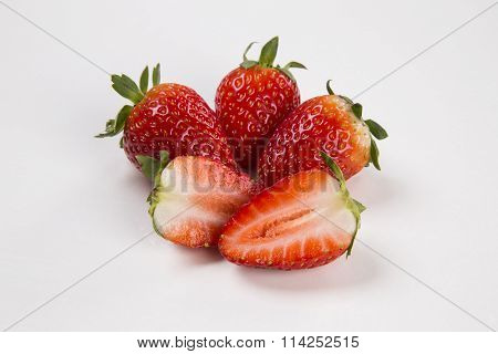 A Strawberry Cut In A Half In Front Of Three Entire Strawberries