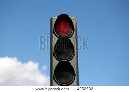 Photo closeup traffic light semaphore with red light-signal stop sign indicator signaling device day time against blue sky background horizontal photo poster
