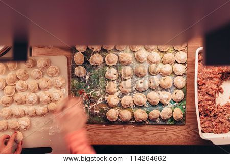 Russian dumplings made by hands and forcemeat with woman hand.