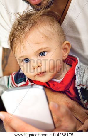 Young cute little boy is watching onto a sellphone with affection embraced by his father.