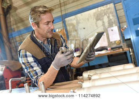 Metal worker in workshop using digital tablet poster