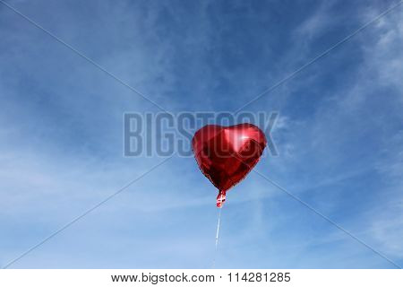 Red Mylar Heart Shaped Valentines Day Helium Filled Balloon floats freely into the Blue Sky with White Clouds.