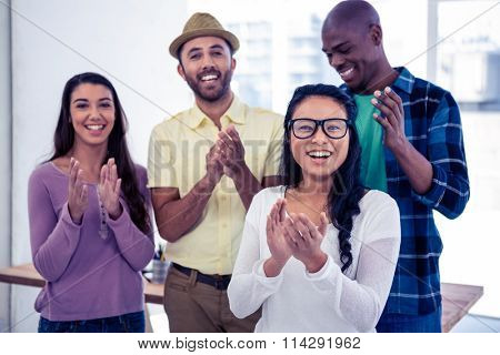 Portrait of businesswoman applauding with team in creative office