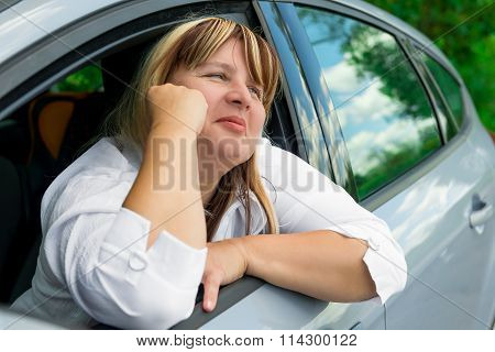 Mature Lady In A Gray Car Resting