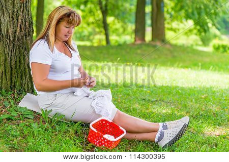 50-year-old Woman Knitting In The Summer Park