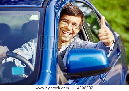Young happy hispanic man wearing glasses sitting inside car, holding steering wheel,  showing thumb up hand gesture through car window and laughing - new drivers concept