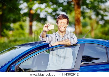 Young hispanic man wearing glasses and jeans shirt holding out his driving license and laughing against blue car outdoors - new drivers concept