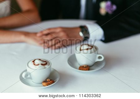 Bride's And Groom's Hands Holding Each Other On A Table With Two Capiccino