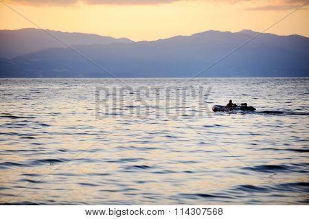 Fisherman Driving A Boat On Ohrid Lake At Sunset