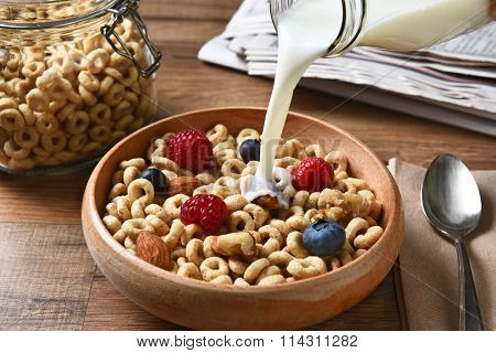 High angle view of a bowl of breakfast cereal with blueberries, raspberries and nuts. A bottle of milk is pouring into the bowl