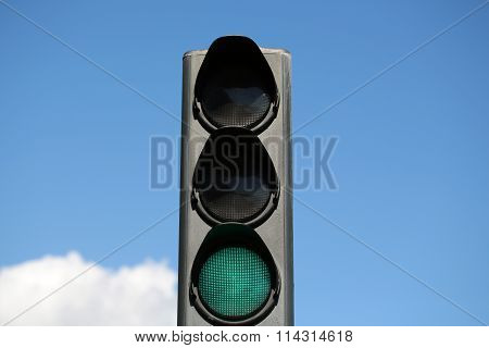 Photo closeup traffic light semaphore with green go light-signal indicator signaling device day time against blue sky background horizontal photo poster