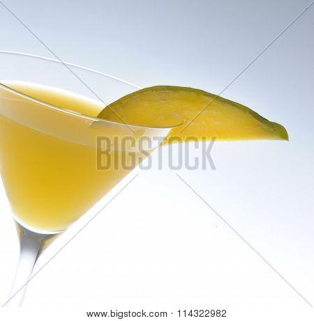Luxurious yellow cocktail with mango garnish