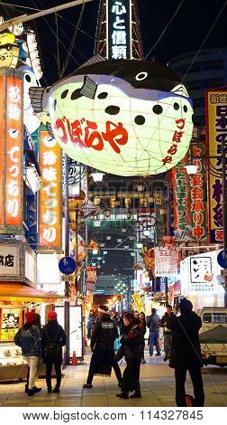 Osaka Japan - March10 2015: People walking around shinsekai tsutenkaku restaurant street area with landmark fish latern neon sign