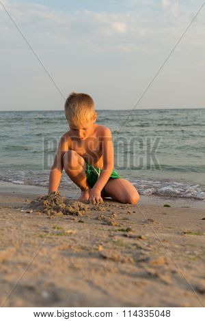 Boy 5 years playing in the sand, sea vacation