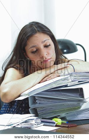 Hispanic brunette office worker sitting by desk and lying over pile of archive files looking tired