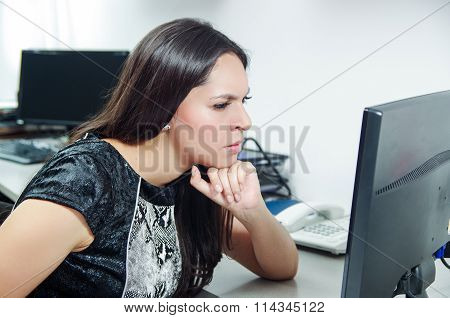 Hispanic brunette sitting by office desk working on computer with occupied and worried facial expres
