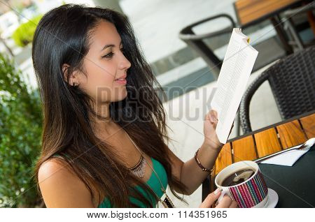 Pretty brunette model wearing turquoise singlet sitting by cafeteria table reading paper while enjoy